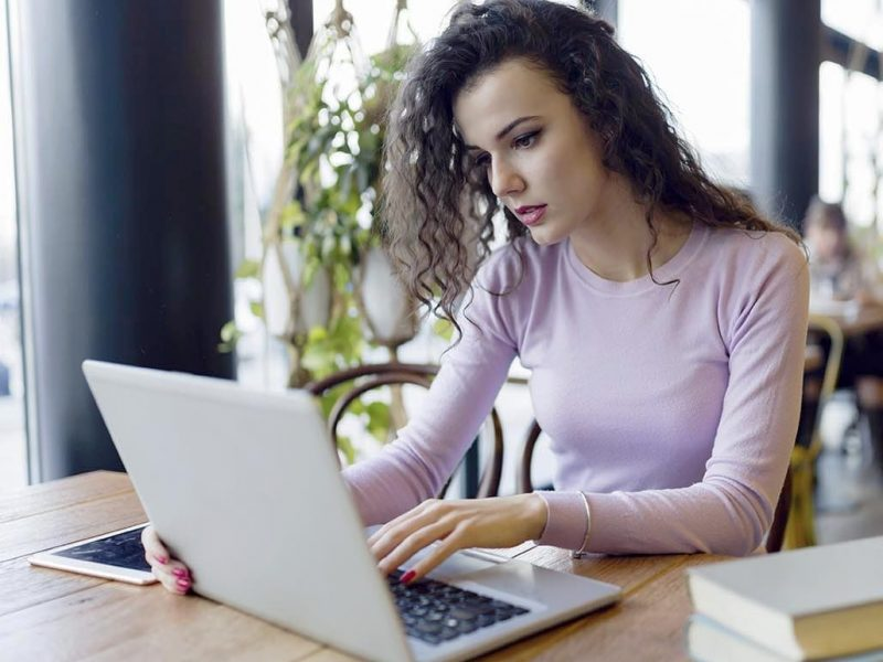 young-woman-working-on-laptop-in-coffee-shop-K9HY7LD-1.jpg